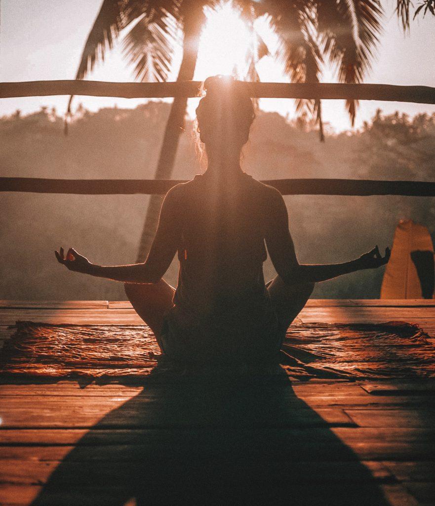 Femme méditant au coucher du soleil